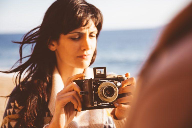 frau-kamera-analog-aufziehen-strand