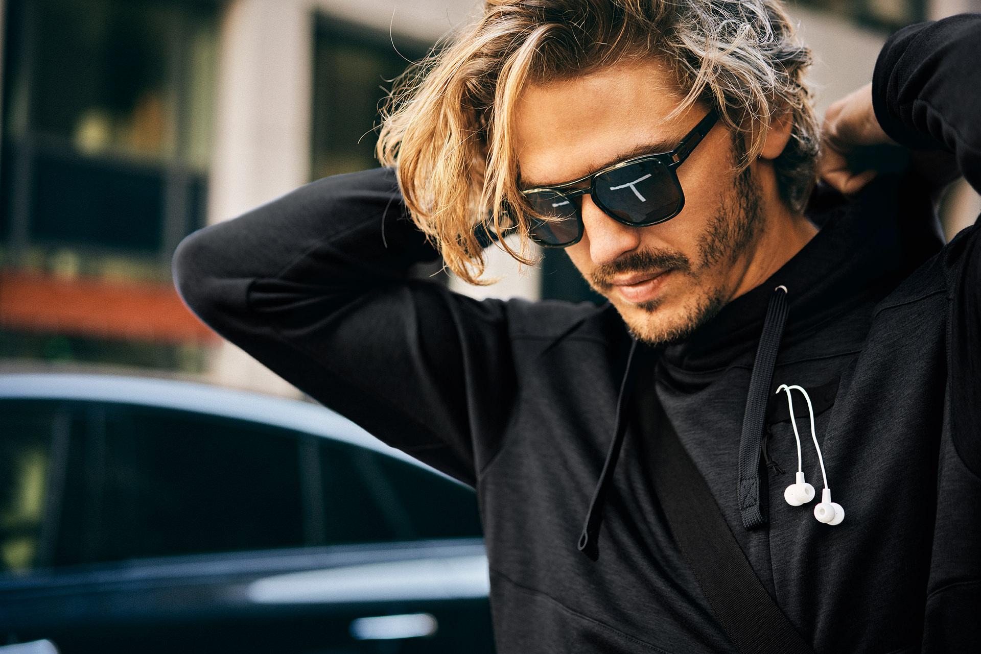 mann-sonnenbrille-hoodie-kopfhoerer-stadt