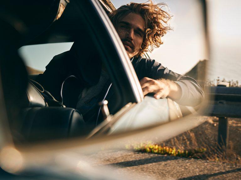 roadtrip-man-car-window-wind