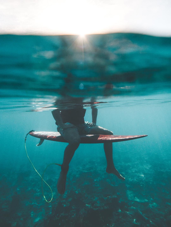surf-board-sitzen-badehose-unterwasser